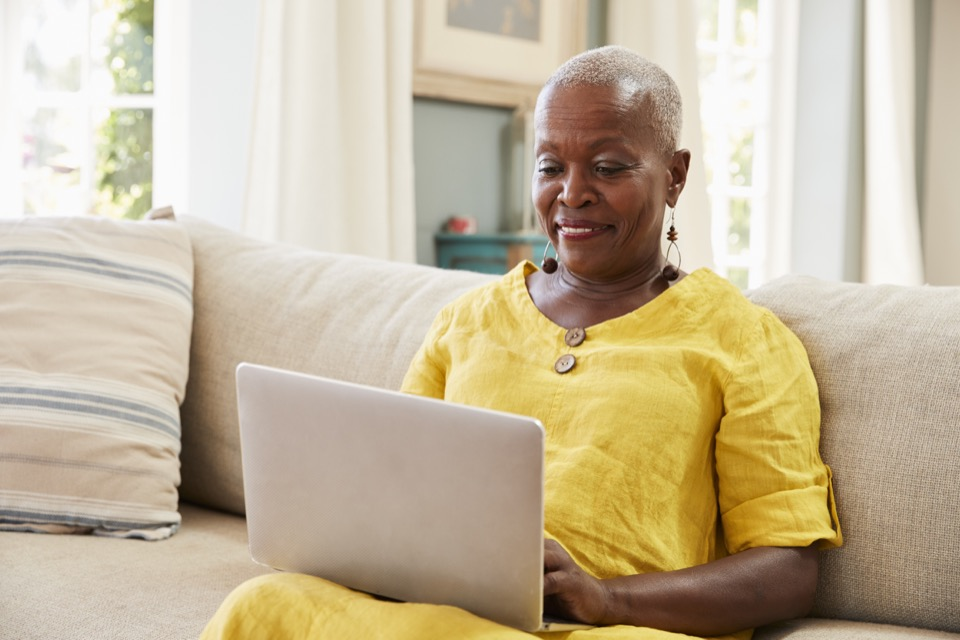 Photo of Senior Woman Sitting On Sofa Using Laptop At Home